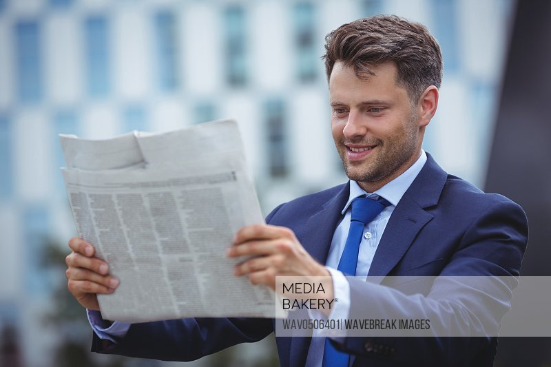 Handsome businessman reading newspaper outside office