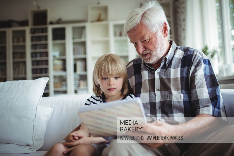 Senior man and her granddaughter looking at a photo album in home