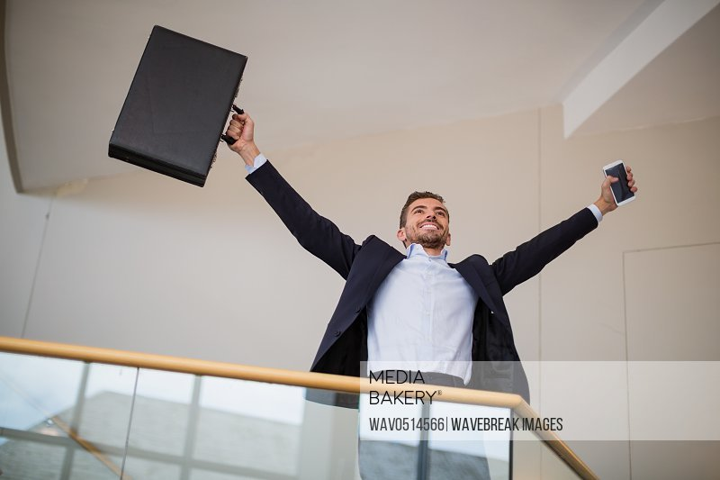 Businessman holding a briefcase and mobile phone cheering