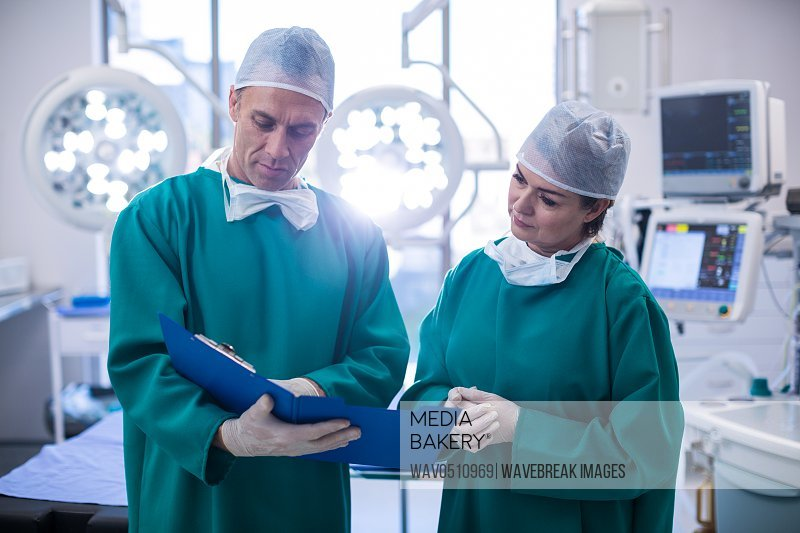 Surgeons discussing over medical reports in operation room at hospital