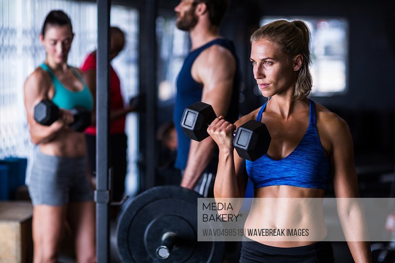 Confident woman holding dumbbells while working out in gym