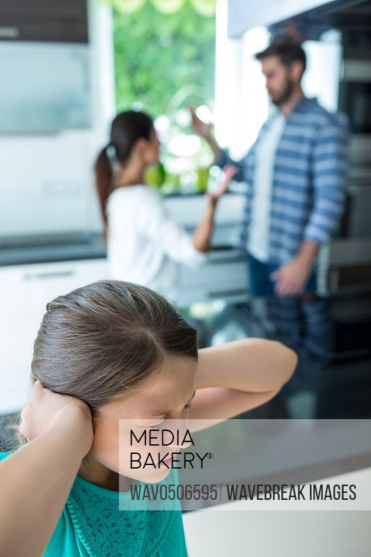 Sad girl covering her ears while parents arguing in background at home