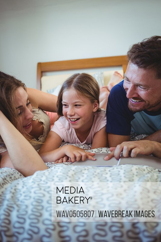 Parents lying with daughter on bed and looking at photo album at home