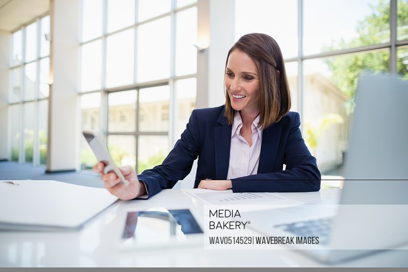 Businesswoman sitting at desk and using mobile phone