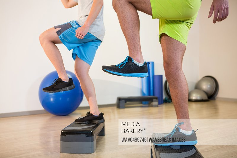 Two men doing step aerobic exercise on stepper in fitness studio
