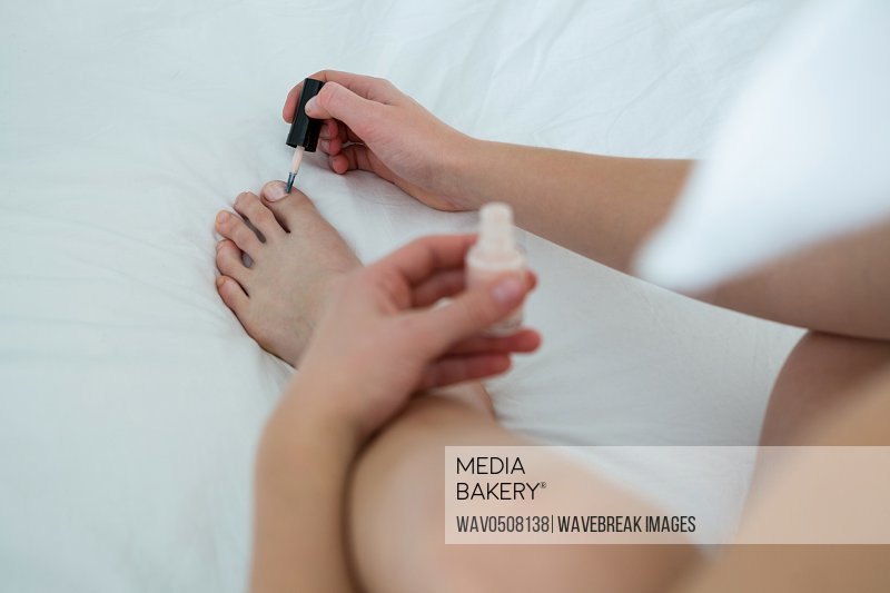 Woman applying nail polish on her toe nails in bedroom at home