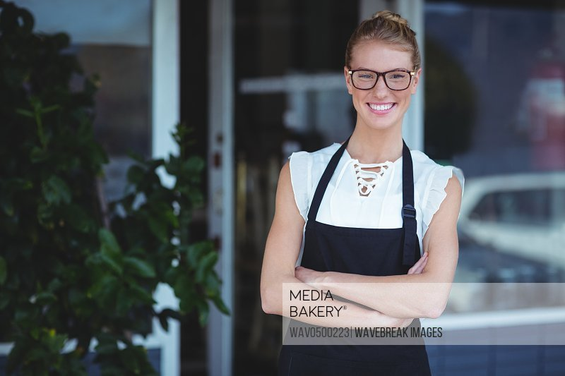 Portrait of smiling waitress standing with arms crossed outside the cafe