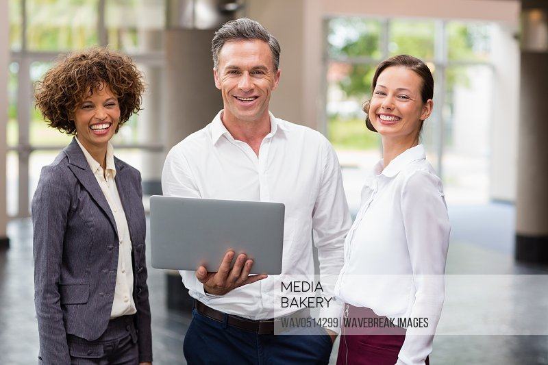 Business executives holding laptop and laughing