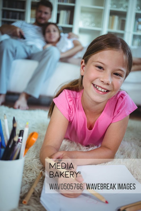 Girl lying on the floor and drawing while parents sitting on sofa
