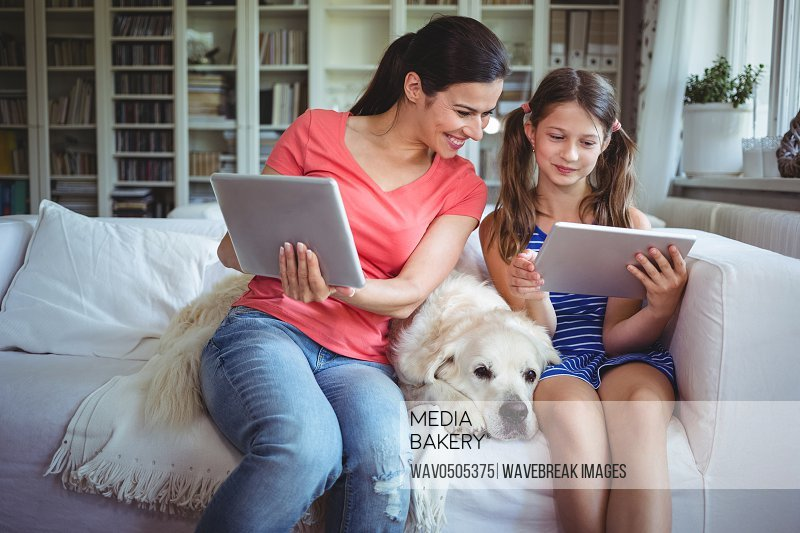 Mother and daughter sitting with pet dog and using digital tablet at home