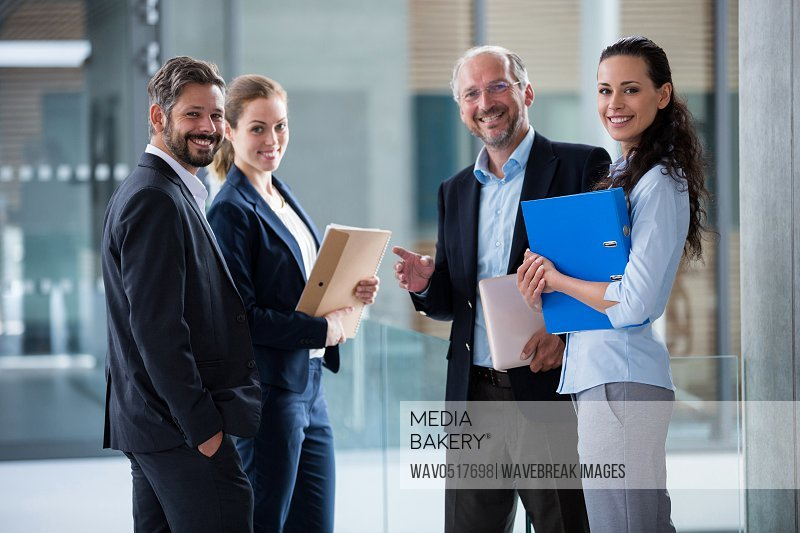 Happy businesspeople standing in office lobby