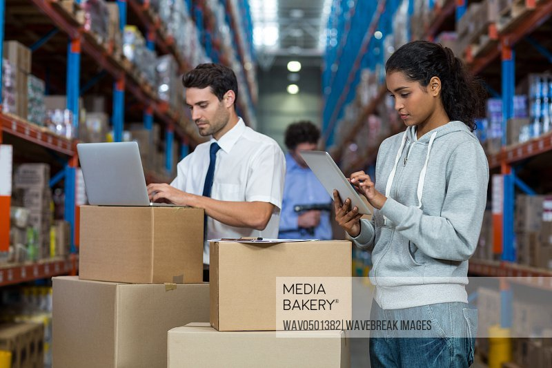 Warehouse worker working on laptop and digital tablet in warehouse