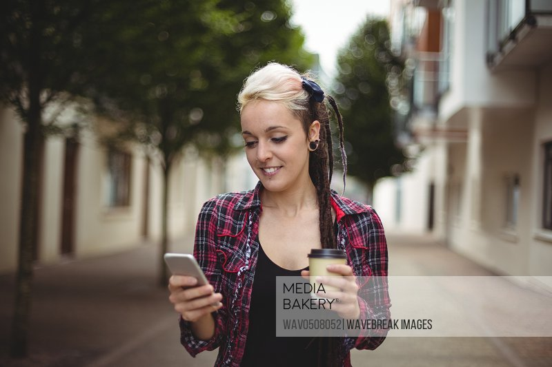 Woman using mobile phone while having coffee on street