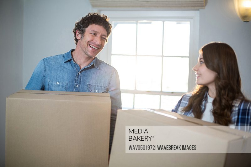 Couple holding cardboard boxes at home