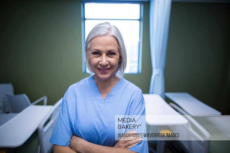 Portrait of nurse standing with arms crossed in hospital