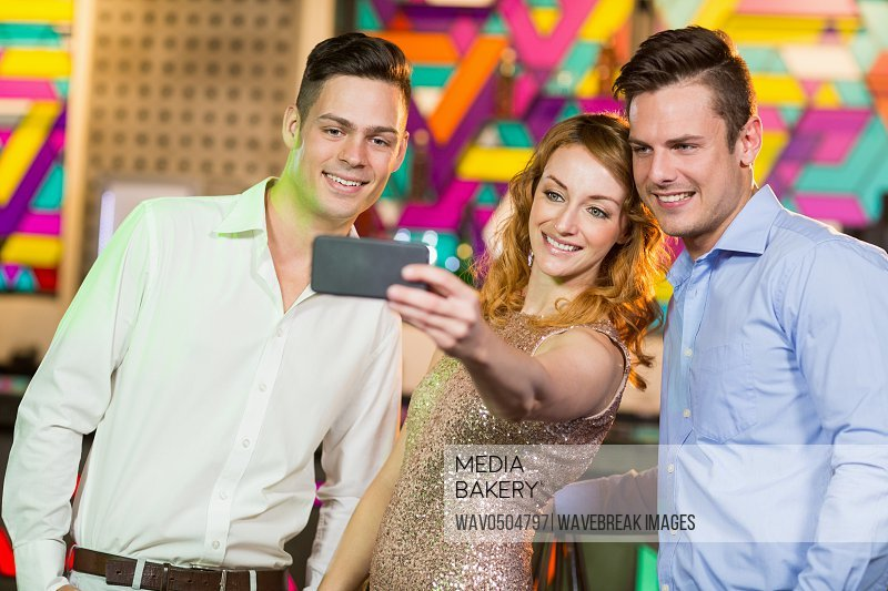 Smiling friends taking a selfie from mobile phone in bar