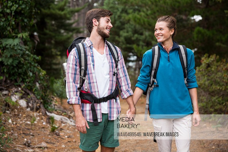 Hiker couple interacting while walking in forest