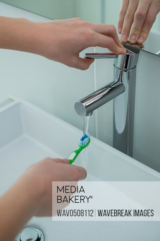 Woman washing toothbrush under sink in bathroom at home