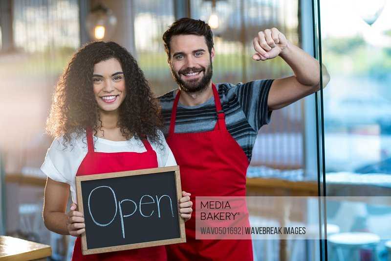 Portrait of waitress and waiter standing with open sign board in cafe