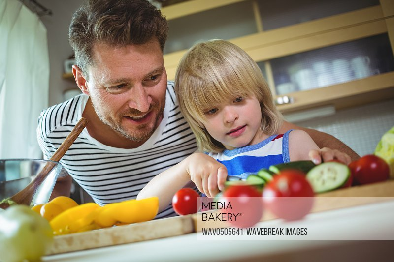 Father and daughter chopping vegetables in kitchen at home