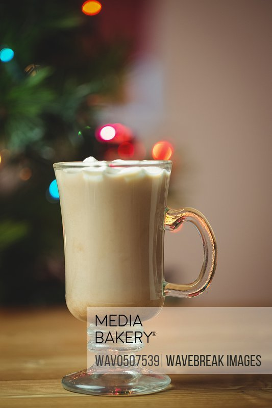 Cup of coffee with marshmallow on wooden table during christmas time