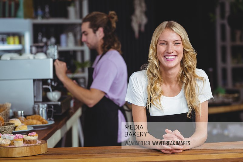 Portrait of smiling waitress standing at counter in cafe