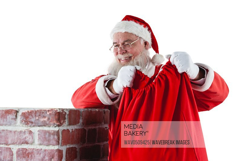 Santa claus placing gift box into a chimney