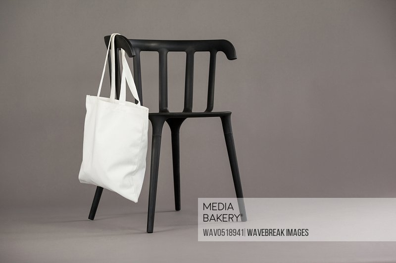 White shopping bag hanging on black chair