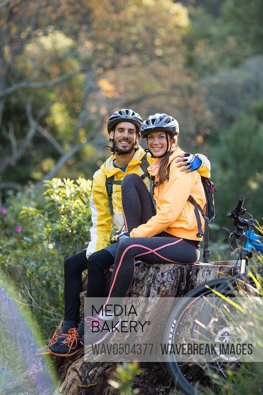 Biker couple sitting on a tree stump in countryside forest