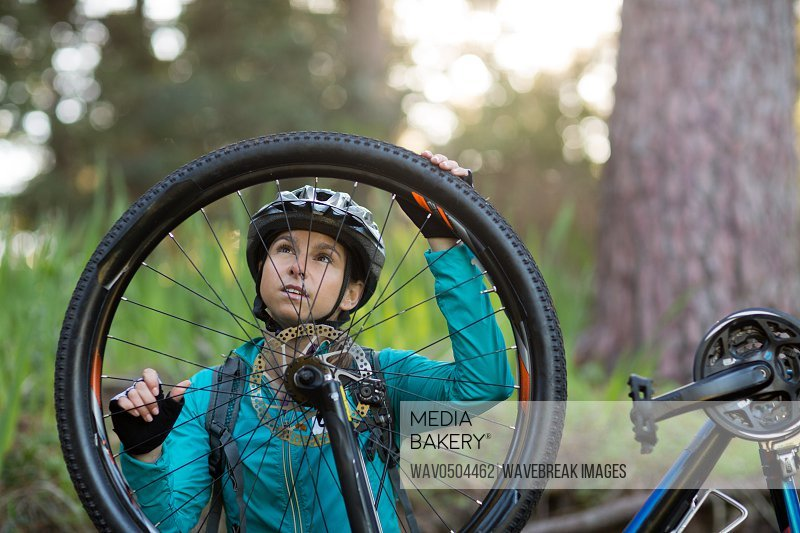 Female biker repairing mountain bike in countryside