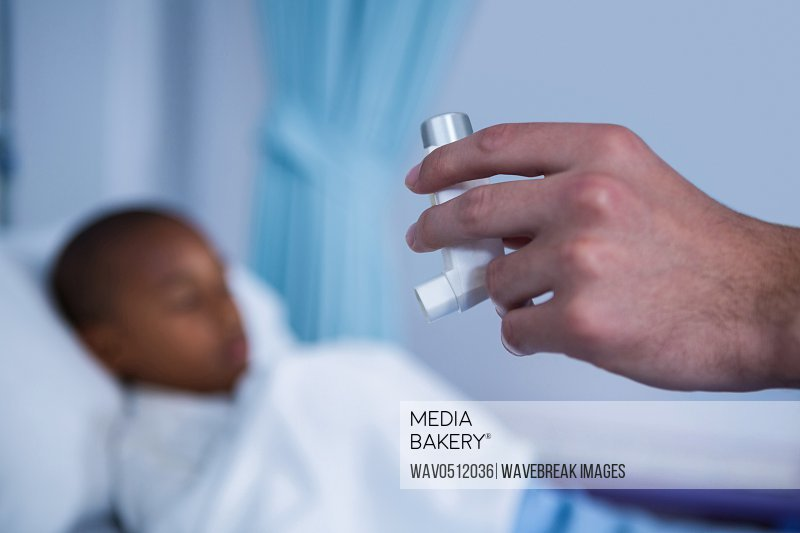 Hand of nurse holding asthma pump in ward at hospital