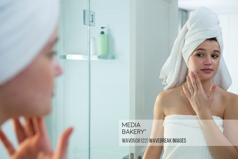 Woman applying moisturizer cream on her face in bathroom at home