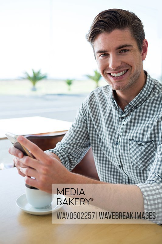 Portrait of smiling man sitting at table and using his mobile phone in coffee shop