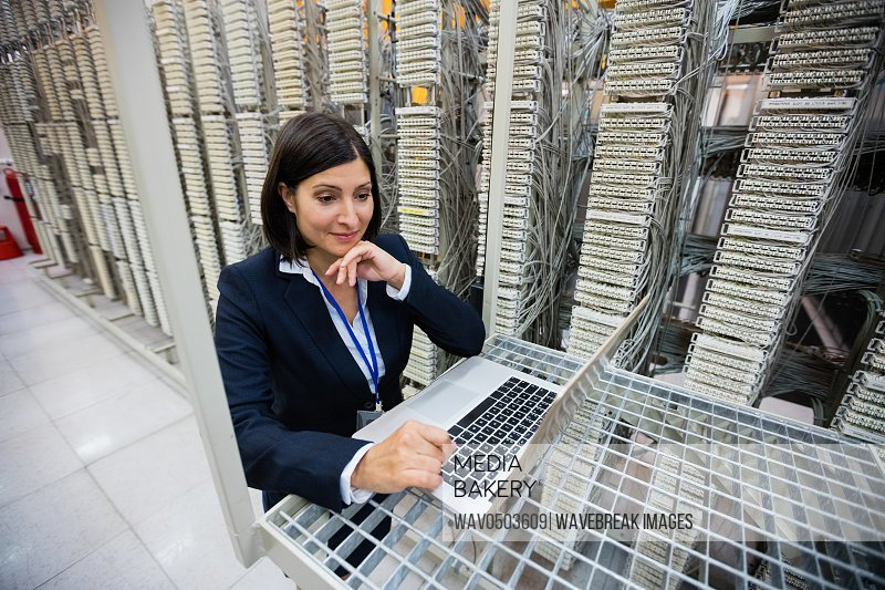 Technician using laptop in server room
