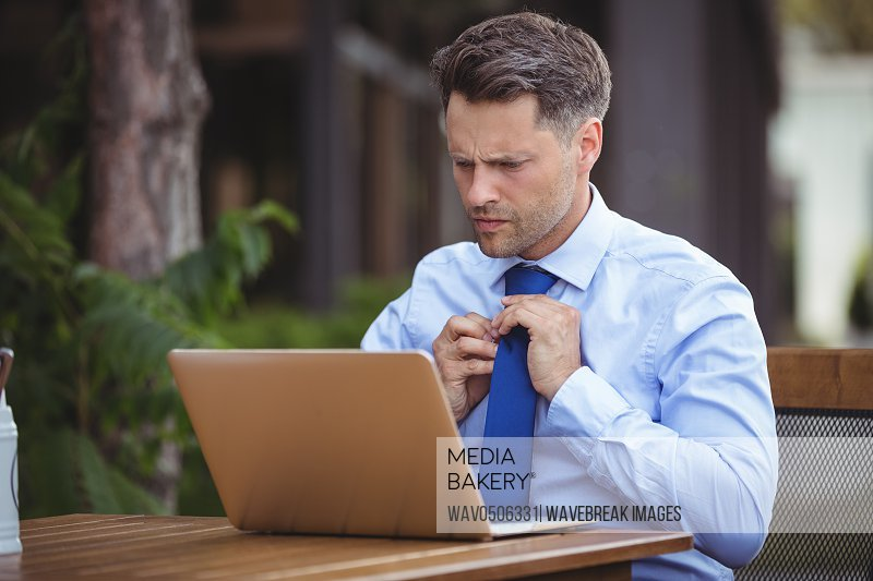 Handsome businessman adjusting tie while using laptop at outdoor cafA?