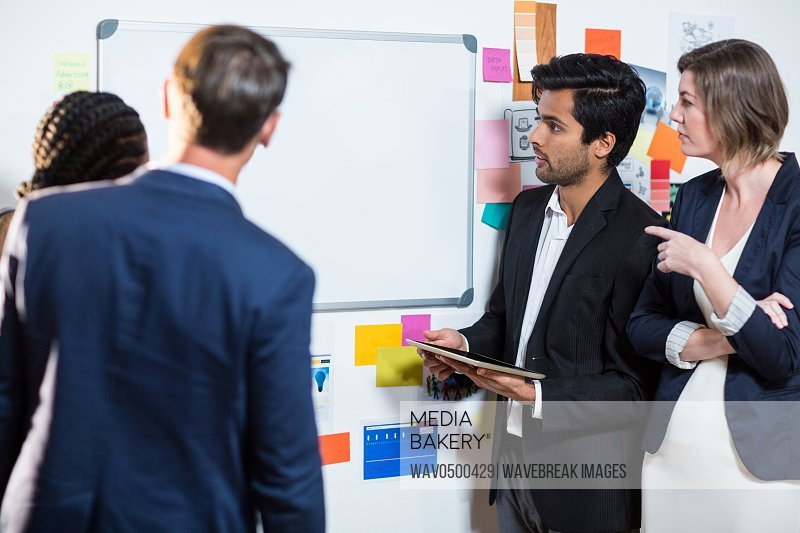 Group of businesspeople looking at whiteboard during a meeting in the office