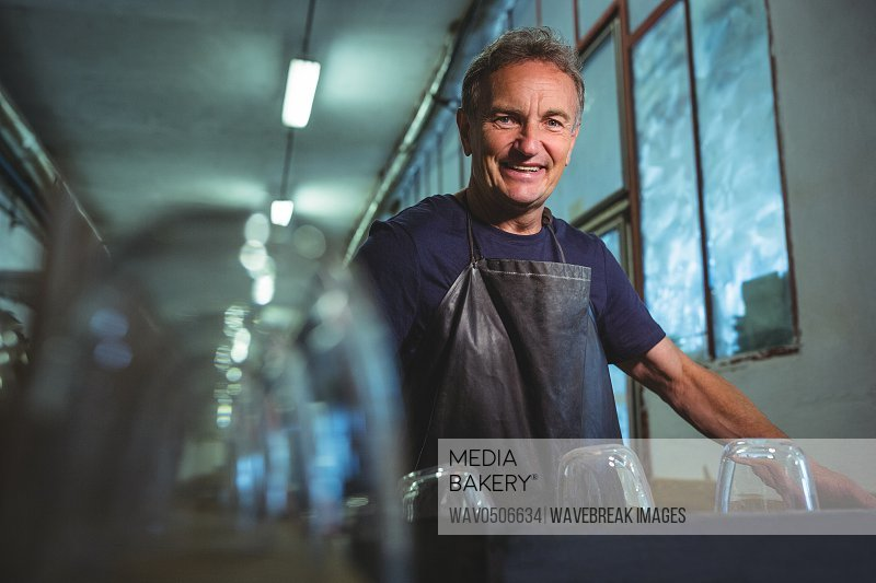 Portrait of smiling glassblower standing in glass blowing factory