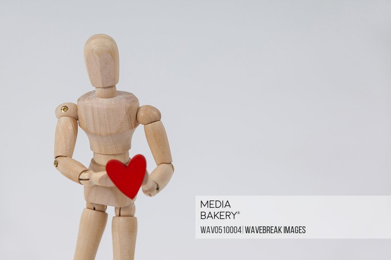 Wooden figurine standing and holding a red heart in front against white background