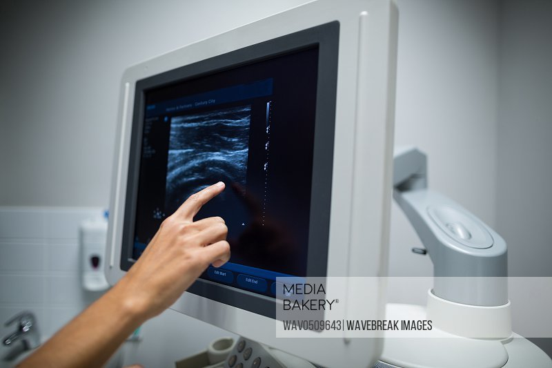 Close-up of nurse pointing at ultrasonic monitor in hospital