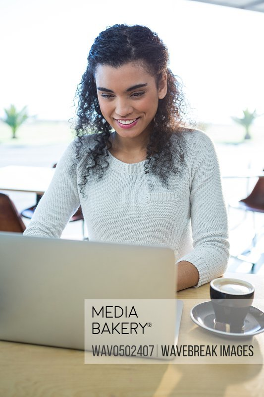 Smiling woman using laptop and a coffee cup on the table in the coffee shop