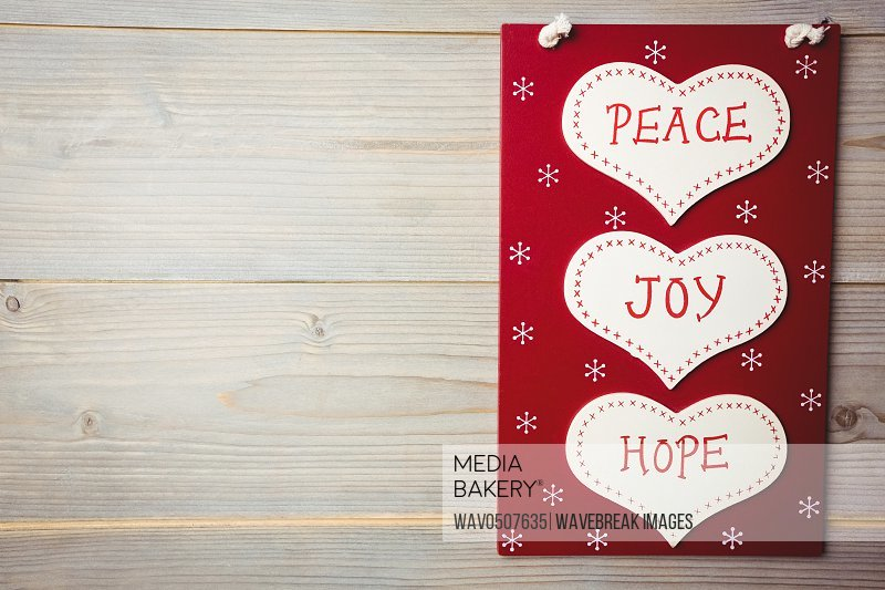 Christmas label with massages of peace joy and hope on wooden table