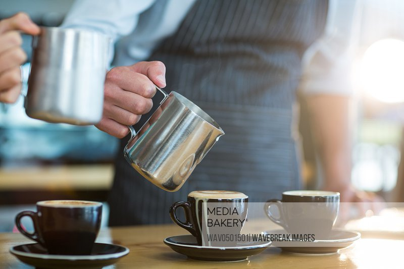 Mid-section of waiter making cup of coffee at counter in cafe
