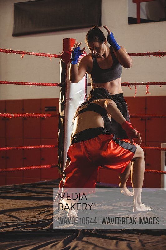 Two female boxers fighting in the ring at fitness studio