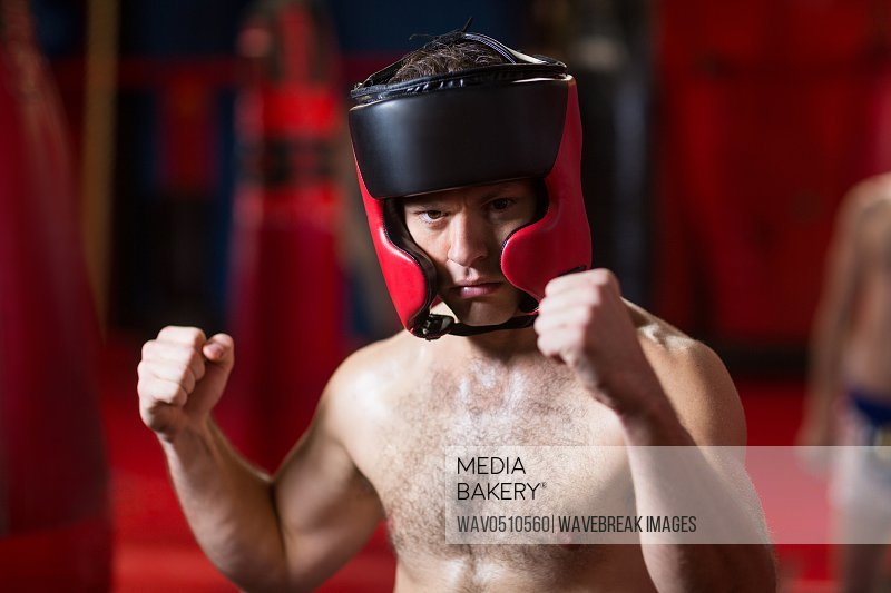 Portrait of confident boxer performing boxing stance in fitness studio