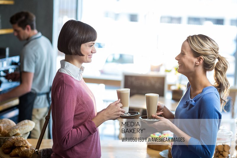 Female friends interacting while having a cup of coffee in cafA?