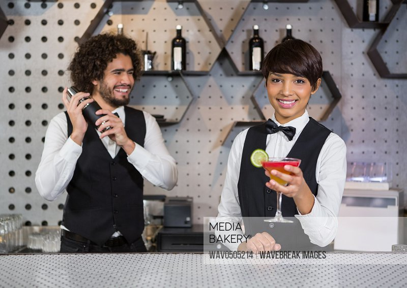 Two bartenders preparing cocktail and serving in bar counter at bar