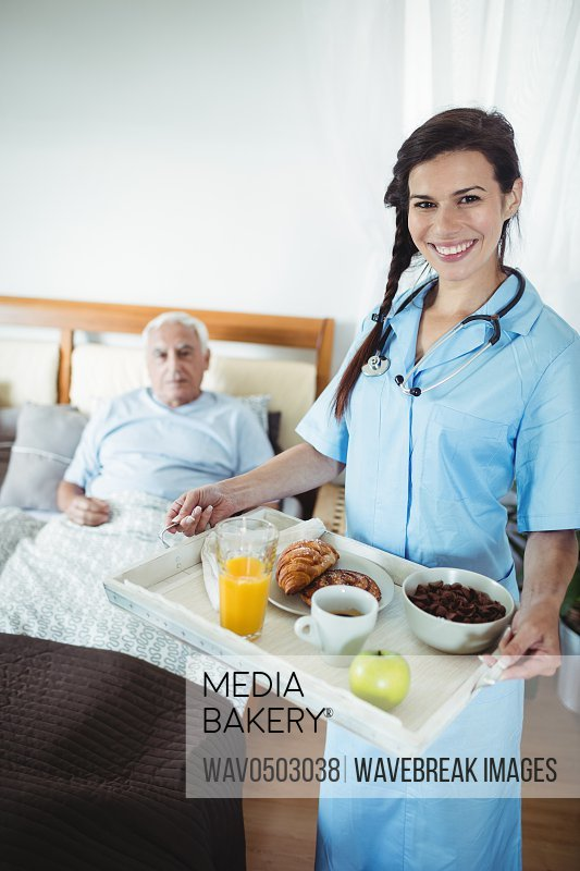 Nurse serving breakfast to senior man at home