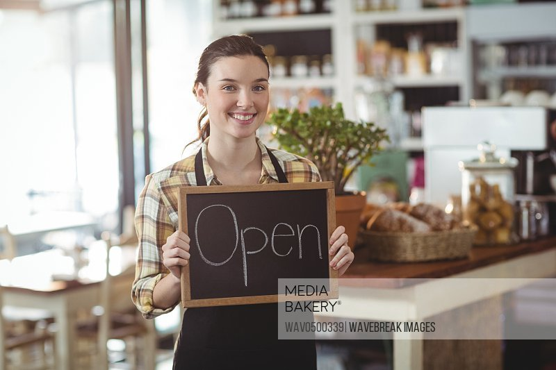 Portrait of waitress showing chalkboard with open sign in cafe