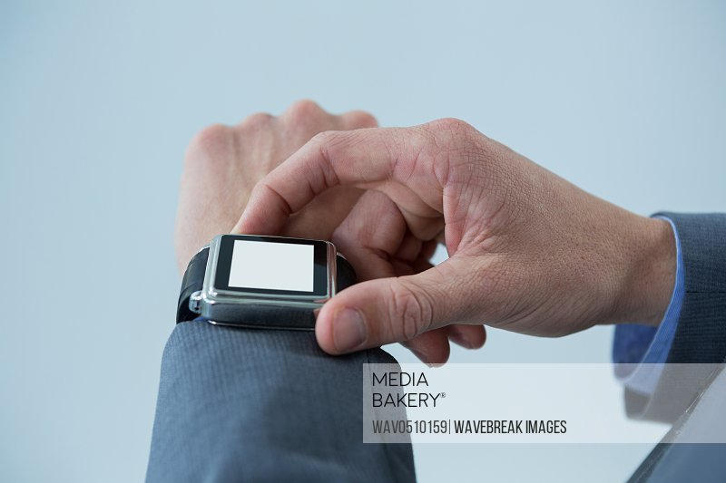Close-up of businessmans hands checking smart watch