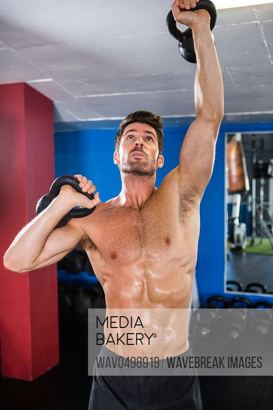 Shirtless athlete exercising with kettlebells in gym